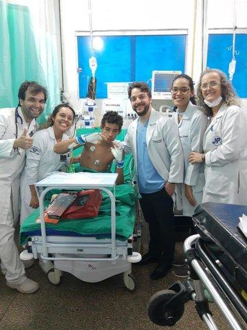 João Victor recebendo as luvas de presente do Dr. Vinicius Ortigosa, com parte da equipe da sala vermelha do JPII - Gente de Opinião